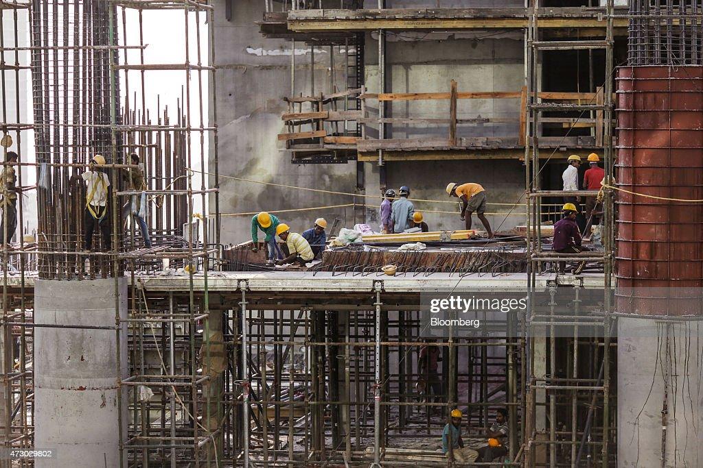 Laborers prepare reinforcing steel on an Indiabulls Real