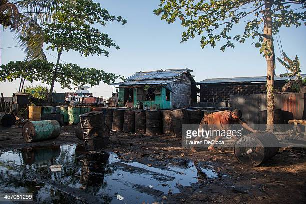 Laborers push drums of recycled oil weighing 240kg on the banks of the Irrawaddy River on December 16 2013 in Yangon Myanmar Large cargo ships on the...