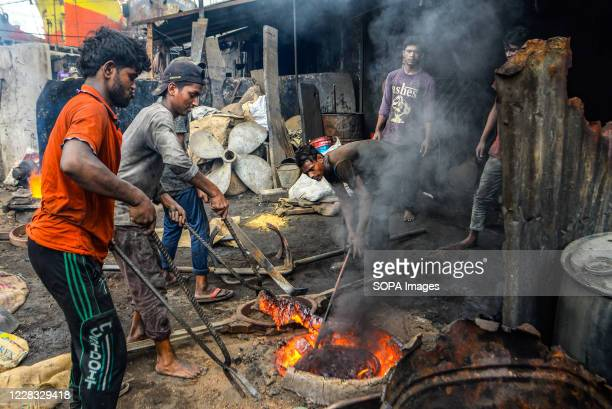 Laborers smelting equipment at a shipyard near the Buriganga River. The shipbuilding industry in Bangladesh is spreading rapidly where workers from...