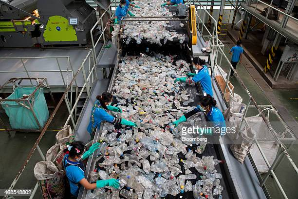 Laborers sort polyethylene terephthalate bottles on a conveyor at the Indorama Polyester Industries Pcl Nakhon Pathom recycling facility operated by...