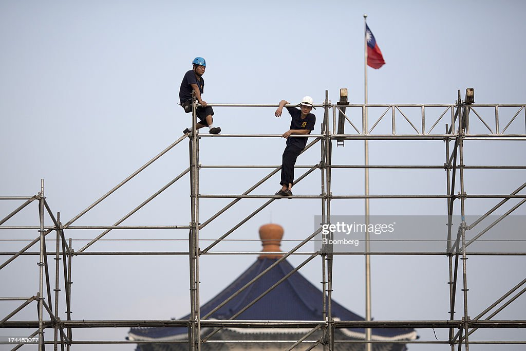 Laborers take a break on scaffolding at the Chiang Kai Shek Memorial Hall plaza in Taipei, Taiwan, on Wednesday, July 24, 2013. Taiwan President Ma Ying-jeou ruled out driving down the Taiwan dollar to boost exports following the currencys rally against the yen and said the government still aims for growth of at least 2 percent this year. Photographer: Jerome Favre/Bloomberg via Getty Images