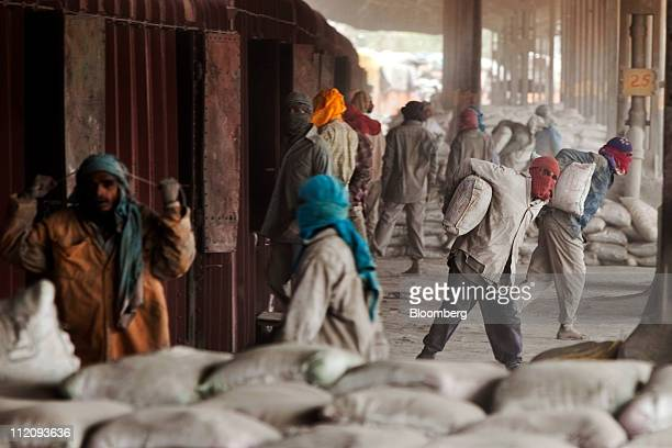 Laborers unload cement bags from freight trains at the Shakur Basti station in New Delhi India on Tuesday April 5 2011 Prime Minister Manmohan...