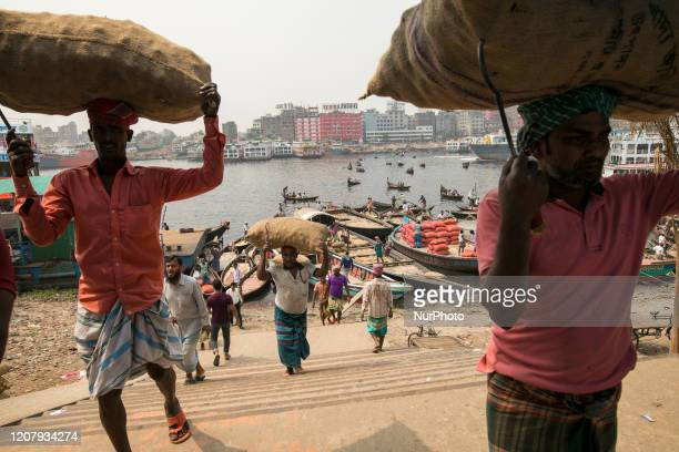 Laborers unload goods from boat in the Buriganga river in Dhaka Bangladesh on March 21 2020 The chemical waste of mills and factories household...
