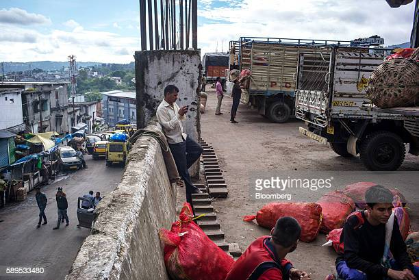 Laborers wait to offload goods from trucks at the Bara Bazar market in Shillong Meghalaya India on Wednesday Aug 10 2016 India's inflation...