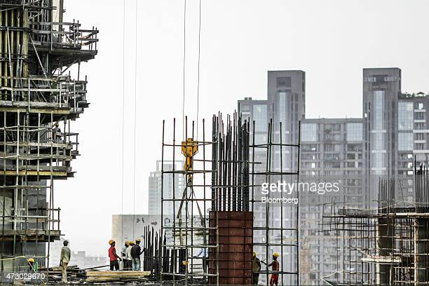 Laborers watch a crane operate on an Indiabulls Real Estate Ltd commercial building construction site in the Lower Parel area of Mumbai India on...