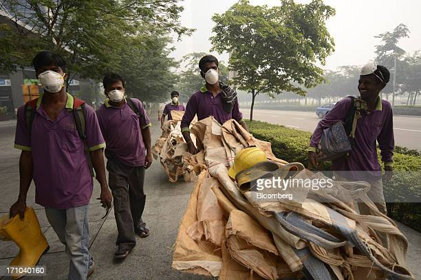 Laborers wear face masks as they transport loads of materials in Singapore, on Friday, June 21, 2013. Singapore's smog hit its worst level,...