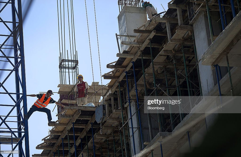Laborers work at a construction site in Guatemala City, Guatemala, on Wednesday, Nov. 23, 211. Foreign direct investment in Guatemala will stagnate this year at about $668 million, after rising 22 percent in 2010, according to the International Monetary Fund (IMF). Photographer: Victor J. Blue/Bloomberg via Getty Images