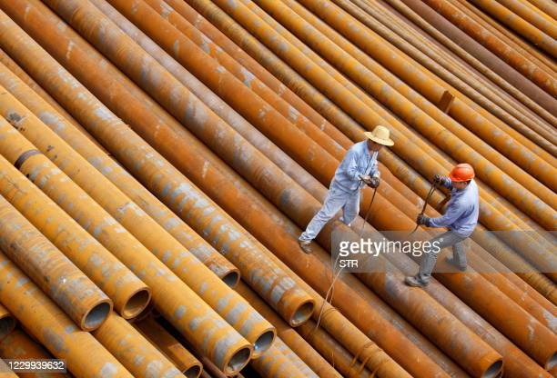 Laborers work at an iron and steel plant in Huaibei, in eastern China's Anhui province on July 31, 2010. Manufacturing in China contracted for the...