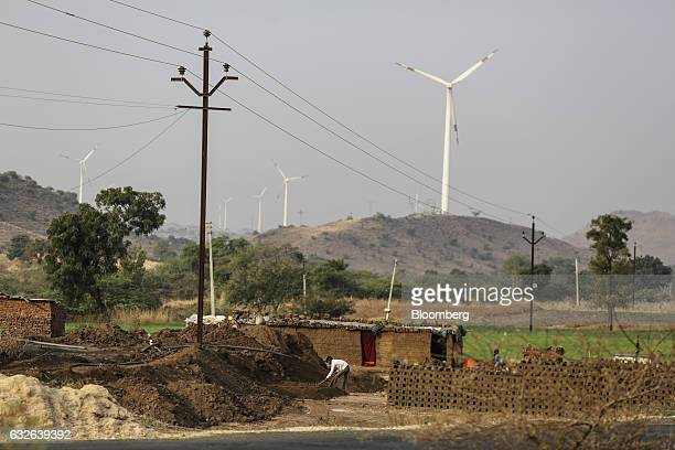 Laborers work below an electricity pole operated by Maharashtra State Electricity Distribution Co as Suzlon Energy Ltd wind turbines stand in the...
