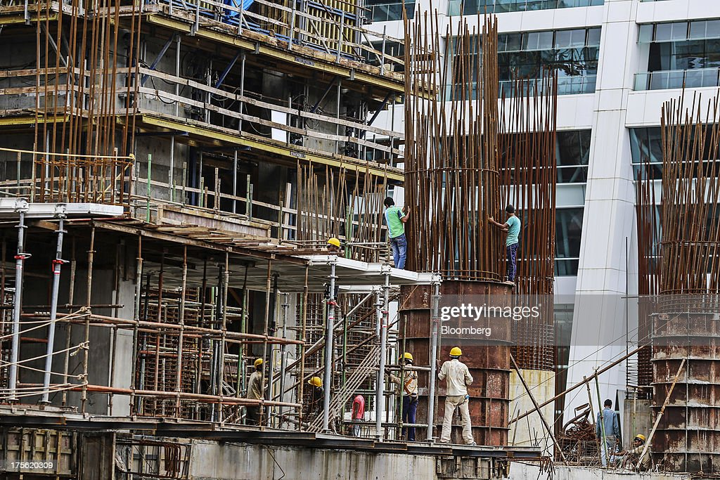 Laborers work on an Indiabulls Real Estate Ltd. commercial building construction site in the Lower Parel area of Mumbai, India, on Sunday, Aug. 4, 2013. India's purchasing managers index (PMI) services figures for July are scheduled for release on Aug. 5. Photographer: Dhiraj Singh/Bloomberg via Getty Images