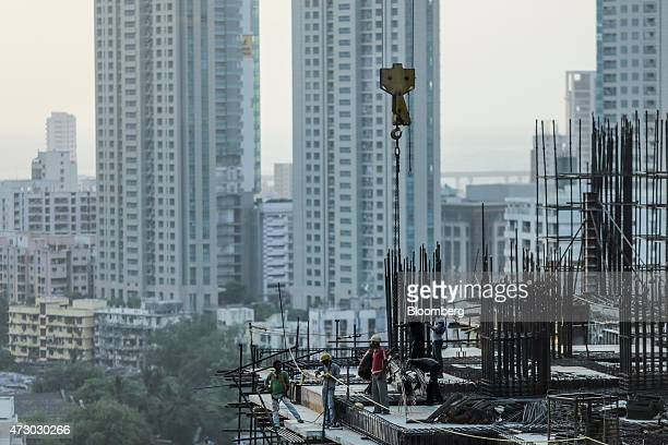 Laborers work on an Indiabulls Real Estate Ltd commercial building construction site in the Lower Parel area of Mumbai India on Monday May 11 2015...