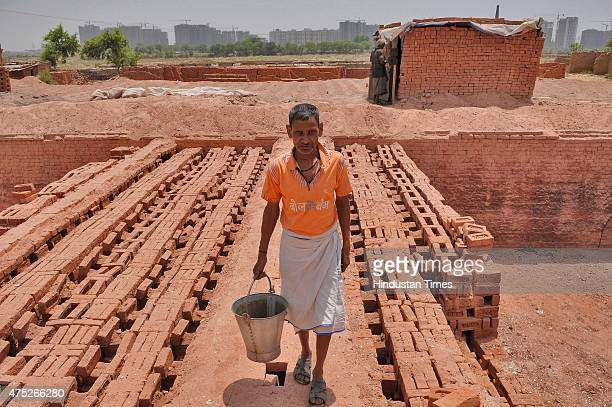 Laborers working at a brick kiln during a hot weather as Delhi/NCR experienced yet another scorching day on the outskirts of New Delhi on May30 2015...