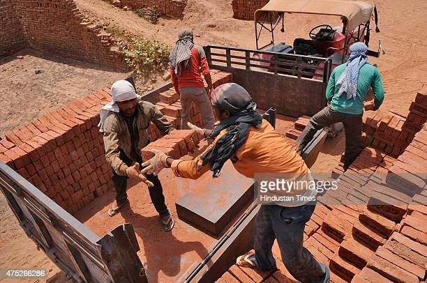 Laborers working at a brick kiln during a hot weather as Delhi/NCR experienced yet another scorching day on the outskirts of New Delhi, on May30,...