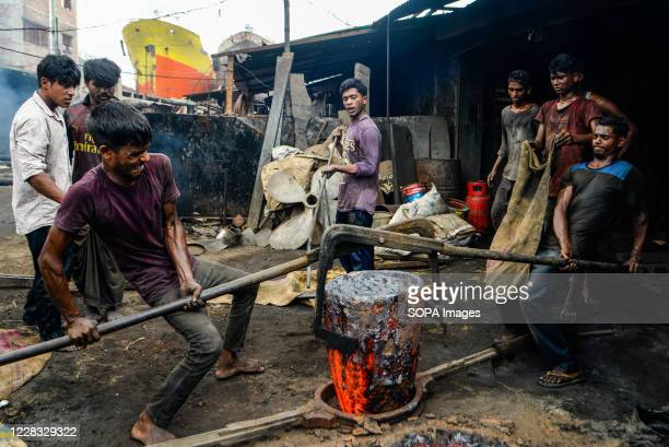 Laborers working at a shipyard near the Buriganga River. The shipbuilding industry in Bangladesh is spreading rapidly where workers from all ages...