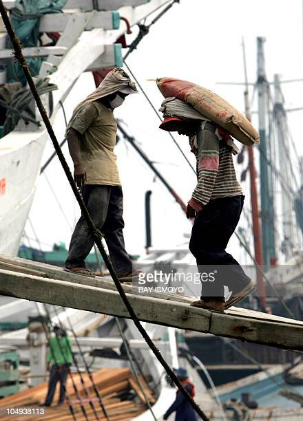Labors are seen loading cement sacks used for domestic needs at the traditional port of Sunda Kelapa in Jakarta 16 April 2007 The country's gross...