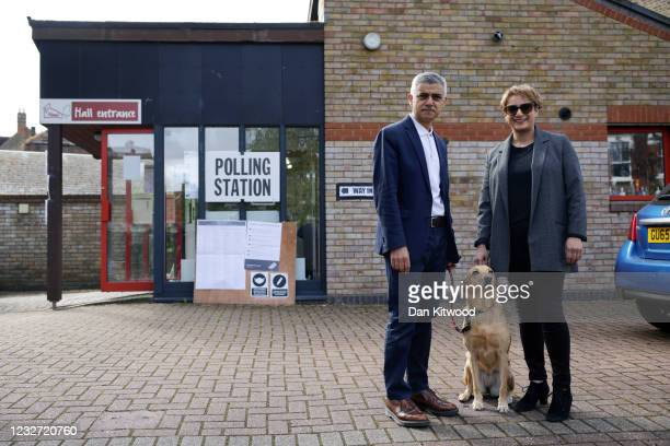 Labour candidate for London Mayor Sadiq Khan poses for a photo with his wife, Saadiya Khan, and their dog Luna outside a polling station in Tooting...