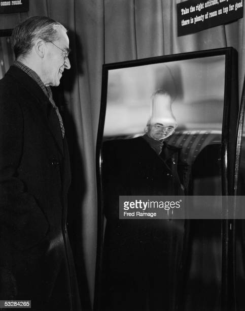 Labour Chancellor of the Exchequer Sir Stafford Cripps views his reflection in a distorting mirror at a COI exhibition in London entitled 'On Our...