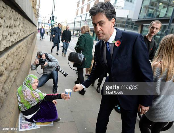 Labour leader Ed Miliband donates money to a woman as he walks to a meeting with UK council leaders at the Town Hall on October 31, 2014 in...