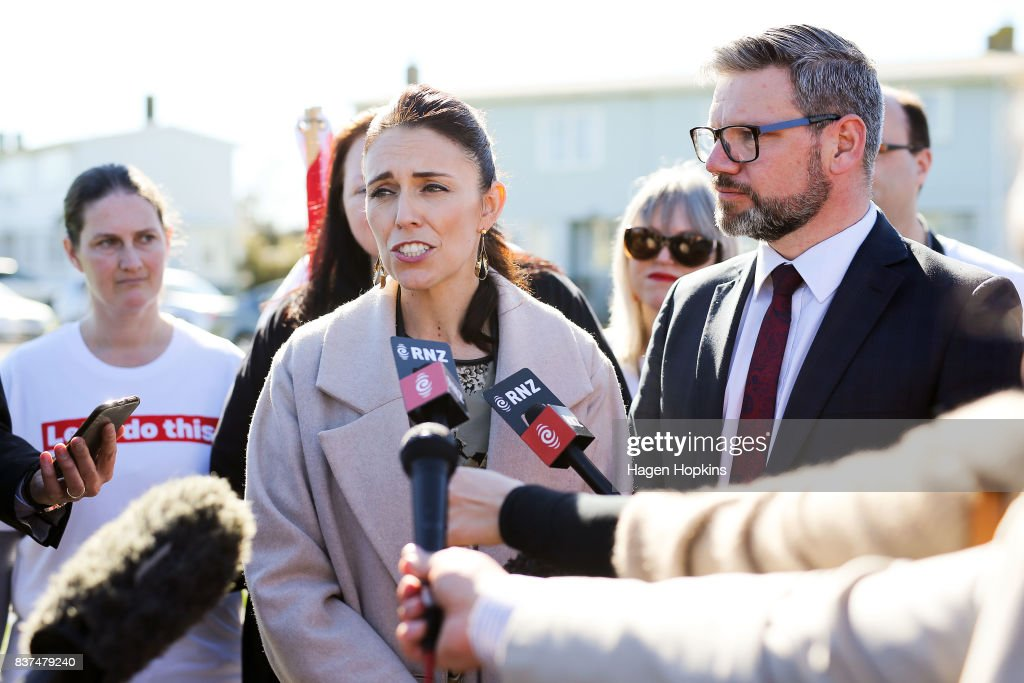 Labour leader Jacinda Ardern speaks to media while MP for Palmerston North, Iain Lees-Galloway, looks on during a housing announcement at Farnham Park on August 23, 2017 in Palmerston North, New Zealand. Ardern announced that Labour will build 149 homes in Palmerston North, a mix of KiwiBuild starter homes for first homebuyers and state houses, to help tackle home affordability and homelessness.