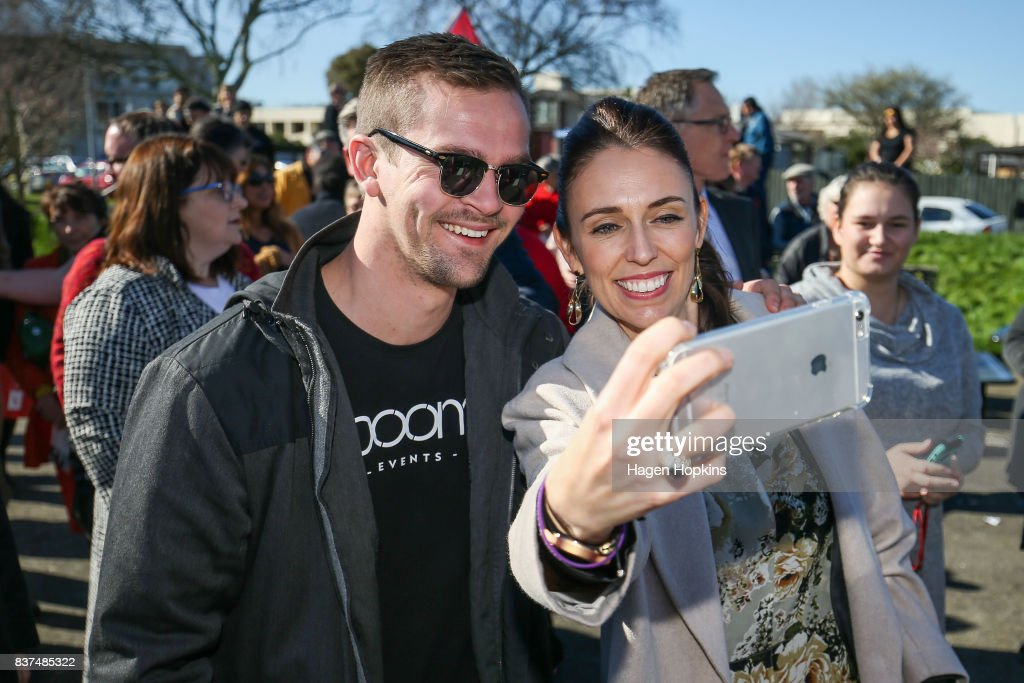 Labour leader Jacinda Ardern takes a selfie with a supporter during a housing announcement at Farnham Park on August 23, 2017 in Palmerston North, New Zealand. Ardern announced that Labour will build 149 homes in Palmerston North, a mix of KiwiBuild starter homes for first homebuyers and state houses, to help tackle home affordability and homelessness.