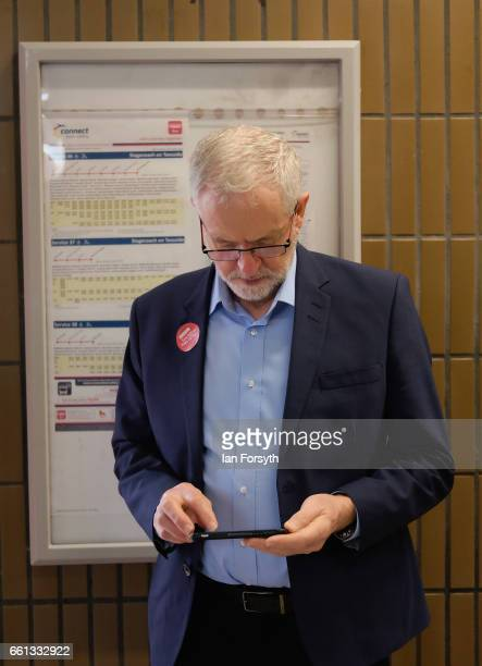 Labour leader Jeremy Corbyn checks his phone as he waits to take a ride on the number 36 bus from Middlesbrough to Stockton on Tees on March 31 2017...