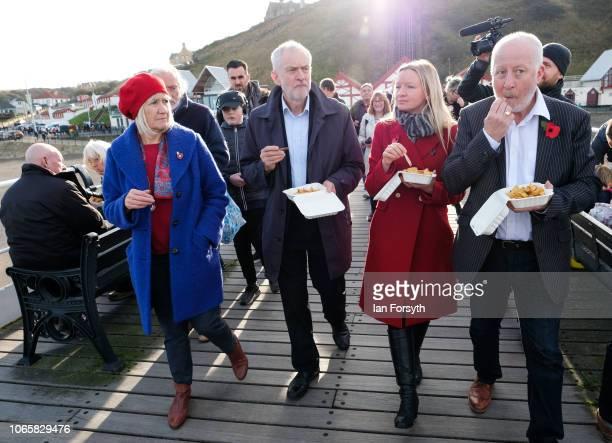 Labour leader Jeremy Corbyn eats chips as he walks along Saltburn pier with Sue Jeffrey Leader of Redcar and Cleveland Borough Council Lauren...