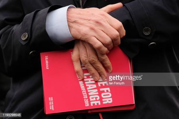 Labour leader Jeremy Corbyn holds the party's manifesto as he speaks to supporters during a stump speech at the Sporting Lodge Inn on December 11...
