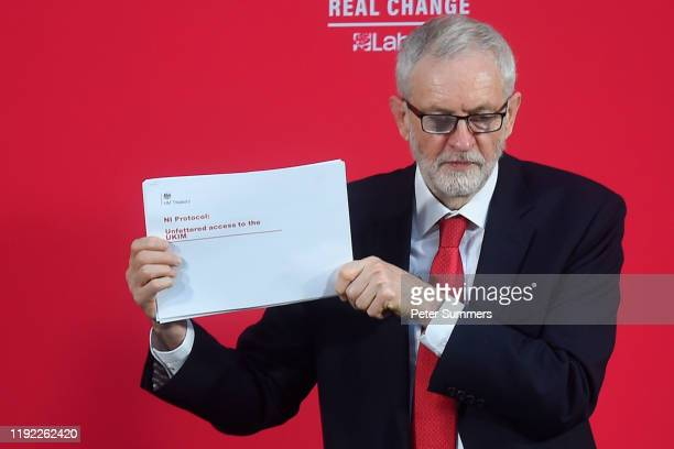Labour leader Jeremy Corbyn holds up a government document as he delivers a speech onstage on December 6 2019 in London England Mr Corbyn announced...
