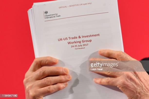 Labour leader Jeremy Corbyn presents documents related to postBrexit UKUS Trade talks as he speaks during an election policy announcement on the NHS...