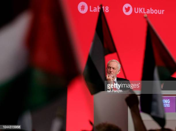 Labour Leader Jeremy Corbyn sits on stage as delegates wave Palestinian flags during a speech about the situation in Palestine on day three of the...