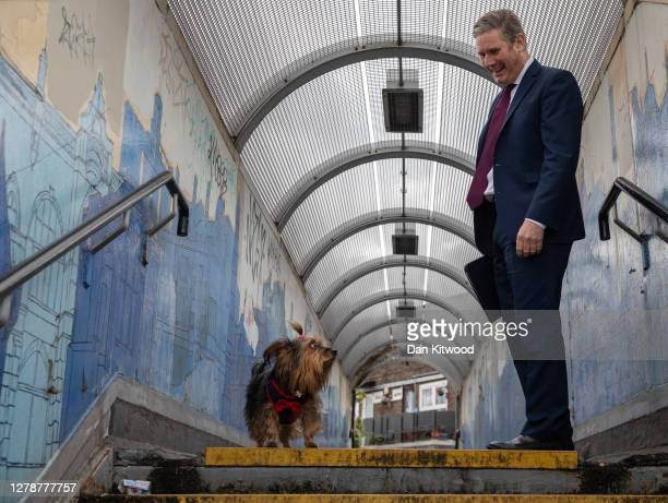 Labour leader Keir Starmer speaks to a member of the public after bumping into her dog Lucy the terrier on a footbridge after a surgery visit on...