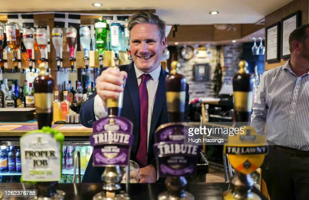 Labour Leader Sir Keir Starmer pulls a pint behind the bar before meeting with local business leaders at the Chainlocker pub in Falmouth where he...