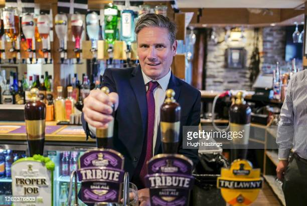 Labour Leader Sir Keir Starmer pulls a pint of Tribute behind the bar before meeting with local business leaders at the Chainlocker pub in Falmouth...