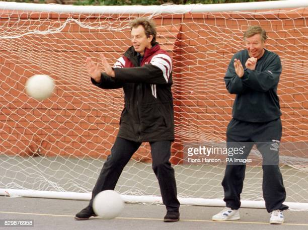 Labour leader Tony Blair parries a shot at goal as Manchester United manager Alex Ferguson takes cover behind during a visit today to Devonshire Road...