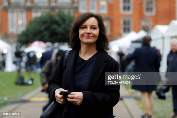 Labour MP Caroline Flint reacts as she walks through thhe temporary media area set up opposite the Houses of Parliament in central London on January...