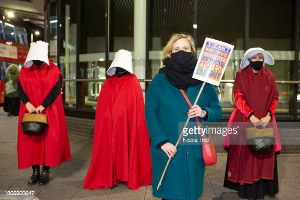 Labour MP for Walthamstow Stella Creasy supports Reclaim These Streets Vigil as she poses with protesters dressed as Handmaidens in red cloaks and...