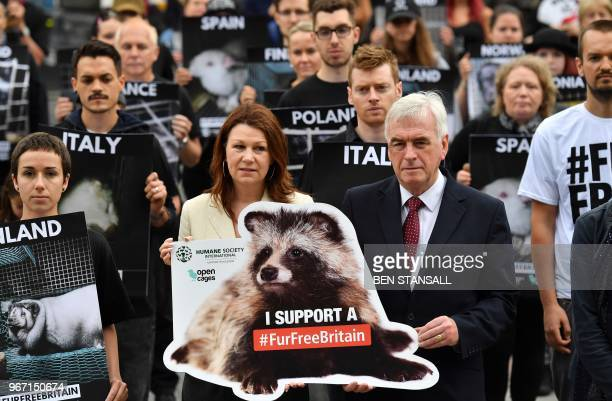 Labour MP Sue Hayman and Labour Party Shadow Chancellor John McDonnell hold a placard as they pose for a photograph with antifur demonstrators as...