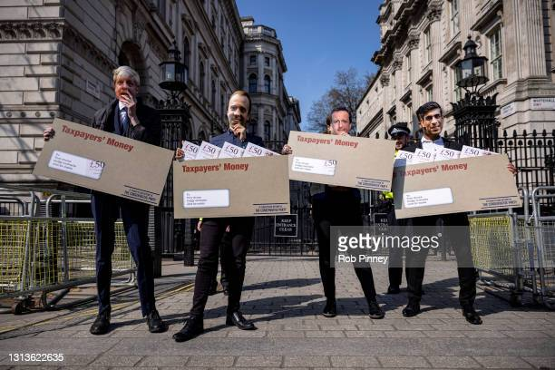 """Labour Party campaigners outside Downing Street during a stunt in which they carried envelopes labelled """"Taxpayer's Money"""" while dressed as..."""