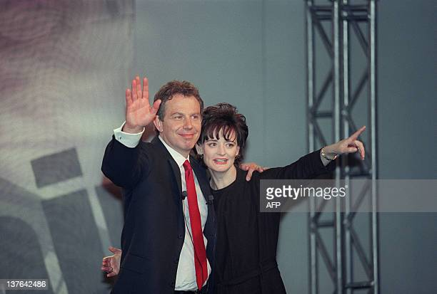 Labour Party leader and new British Prime Minister Tony Blair and his wife Cherie Blair wave and smile at party workers and supporters after their...