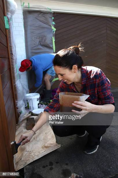 Labour party leader Jacinda Ardern and her partner Clarke Gayford paint the fence of their Pt Chevalier house on September 23 2017 in Auckland New...