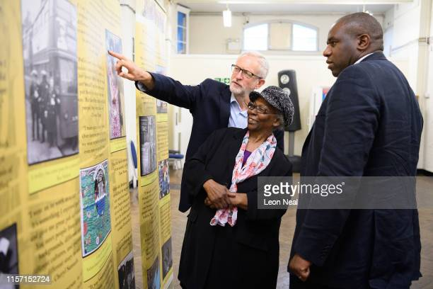Labour Party leader Jeremy Corbyn and David Lammy MP talk with Gloria Byer as they look at photographs of Windrush migrants at the Cardinal Heenen...