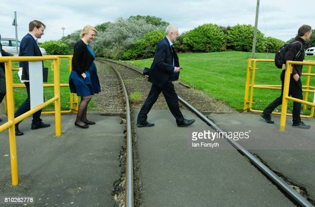 Labour Party leader Jeremy Corbyn crosses over a railway line during a visit to a British Steel manufacturing site to tour the facility and meet...