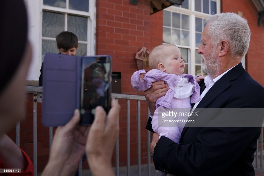 Labour Party Leader Jeremy Corbyn has his photograph taken with a baby before talks to members of Women Against State Pension Inequality Campaign (WASPI) during his visit to Cleveleys Community Centre on August 18, 2017 in Blackpool, England. Jeremy Corbyn is touring the UK visiting marginal seats.