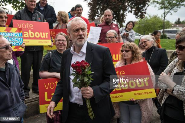 Labour Party leader Jeremy Corbyn holds red roses given to him by activists and supporters as he visits a local shopping arcade on May 4 2017 in...