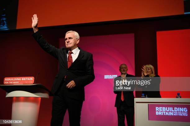 Labour Party leader Jeremy Corbyn looks on as Shadow Chancellor of the Exchequer John McDonnell receives applause following his address to delegates...
