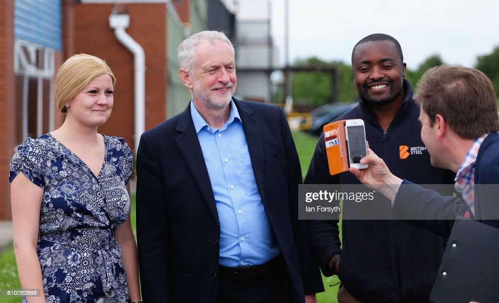 Labour Party leader Jeremy Corbyn poses for a picture with a staff member (R) and his wife as he visits the British Steel manufacturing site to tour the facility and meet staff on July 7, 2017 in Skinningrove, United Kingdom. The visit was part of a wider tour of the Middlesbrough South and East Cleveland constituency and comes as a recent YouGov survey, the first since the General Election last month, puts the Labour party ahead with 46 percent of the public backing Labour. The Middlesbrough South and East Cleveland constituency was won by Conservative Simon Clarke in the General Election after he beat Labour's Tracy Harvey.