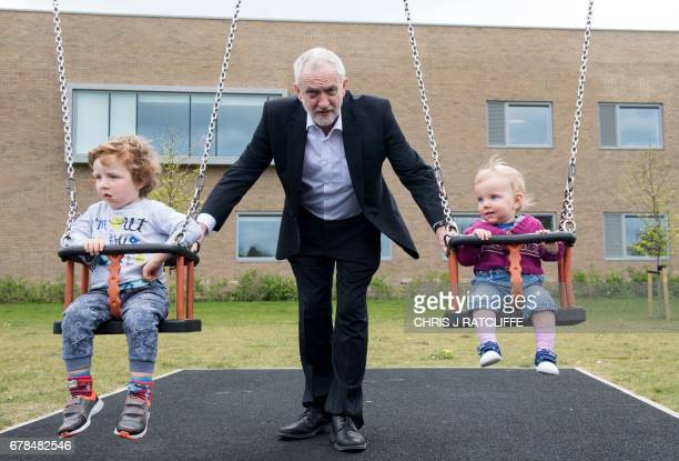 Labour Party leader Jeremy Corbyn pushes the children of Oxford East candidate Anneliese Dodds Isabella and Freddie at a child's playground behind...