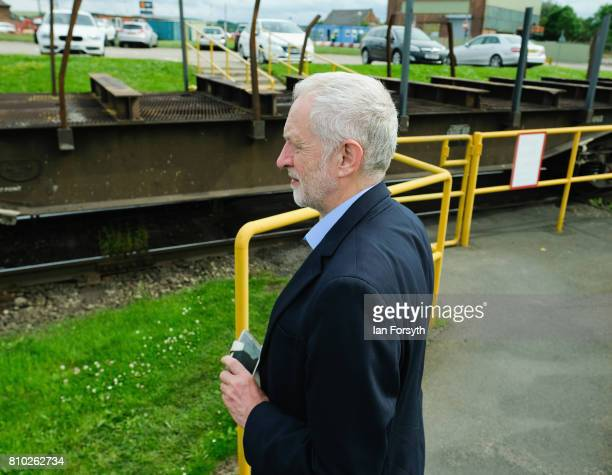 Labour Party leader Jeremy Corbyn waits to cross a railway line during a visit to the British Steel manufacturing site to tour the facility and meet...