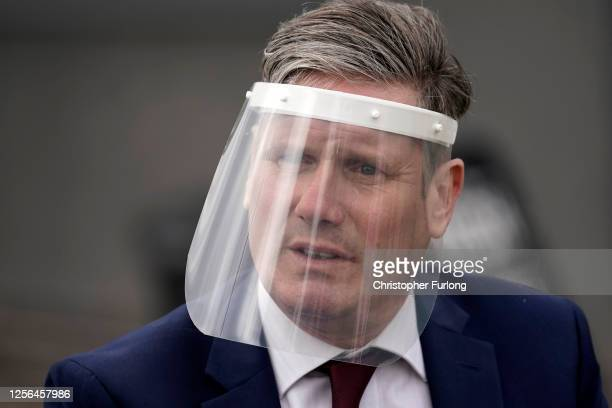 Labour Party leader, Sir Keir Starmer, wears a face visor during talks with care home workers and family members of residents during a visit to Cafe...
