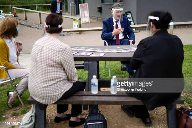 Labour Party leader Sir Keir Starmer wears a face visor during talks with care home workers and family members of residents during a visit to Cafe...